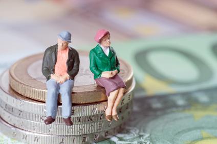 Figuren einer Rentnerin und eines Rentners neben Geld sitzend